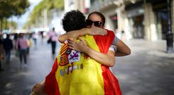 A man wearing a Spanish flag gives 'free hugs' in central Barcelona. Photo: Reuters/ Ivan Alvarado