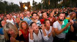 People react as they watch a session of the Catalonian regional parliament on a giant screen at a pro-independence rally in Barcelona, Spain. Photo: Reuters/Ivan Alvarado