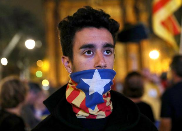 A man reacts as he watches a session of the Catalonian regional parliament on a giant screen at a pro-independence rally in Barcelona, Spain, October 10, 2017. REUTERS/Susana Vera