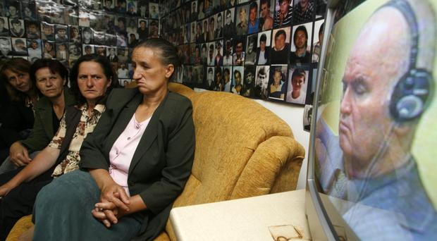 Bosnian Muslim women from Srebrenica, sitting under pictures of victims of the genocide in the town during the 1992-1995 Bosnian war, react as they watch the television broadcast of Ratko Mladic's court proceedings, in Tuzla in 2011. Photo: Reuters