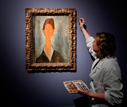A conservator puts the finishing touches on the frame of a portrait of Chaim Soutine – attributed to the Italian artist Modigliani – at the Ducal Palace in Genoa, Italy. Photo: AP