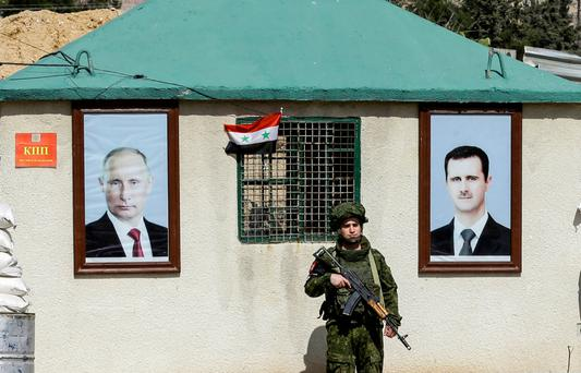 A Russian military policeman stands guard between the portraits of Russian President Vladimir Putin (left) and Syrian President Bashar al-Assad hanging outside a guard-post in Damascus. Photo: Louai Beshara/Getty