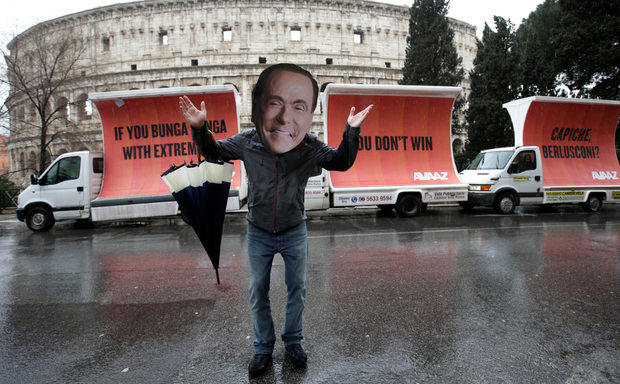 An activist wearing a mask of Forza Italia party leader Silvio Berlusconi poses during a tour, the day after Italy's elections, in Rome. Photo: Reuters