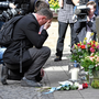 A man pauses to pay his respects as he brings flowers to the scene of the van attack outside the popular pub Grosser Kiepenkerl in Muenster Photo: AP