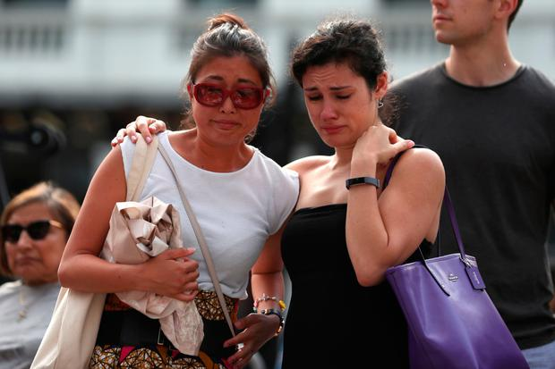 Two women comfort each other during a commemoration service on London Bridge. Photo: Getty
