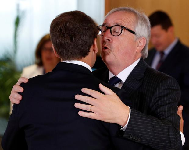 French President Emmanuel Macron is welcomed by European Commission President Jean-Claude Juncker at the emergency summit in Brussels. Photo: Reuters