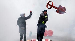 'Street riot: A protester throws a traffic sign during the protest in Brussels.' Photo: Francois Lenoir