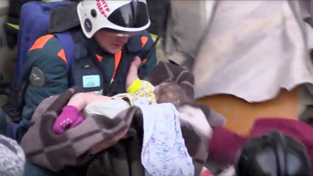 Safe: A rescuer carries the 11-month-old child found in the rubble. Photo: Handout via REUTERS