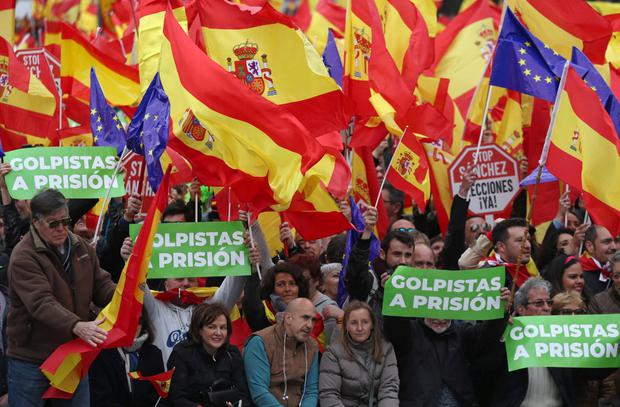 Anger: Protesters hold up placards saying 'Prison for coup leaders' during a rally against Spanish Prime Minister Pedro Sanchez in Madrid. Photo: Reuters