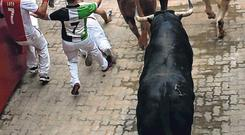 Survivor: A reveller lies injured after falling at the entrance of the bullring in Pamplona. Photo: Jon Nazca/Reuters