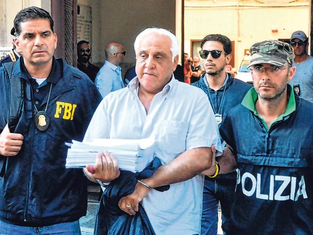 Arrested: An FBI officer and Italian policeman escort Tommaso Inzerillo after he was held in Palermo, Sicily. Photo: AFP/Getty