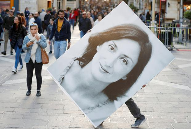 In memory: A protester carries a picture of Daphne Caruana Galizia during a rally outside the Courts of Justice in Valletta, Malta. Photo: Reuters