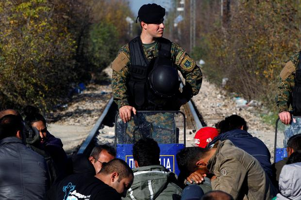 A policeman stands guard on the Macedonian side of the border near the Greek village of Idomeni