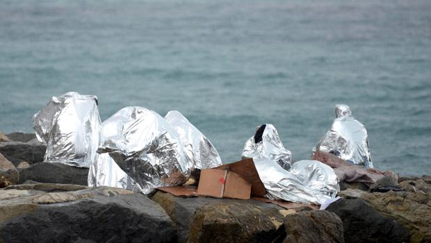 A group of migrants protect themselves with emergency blankets from a sudden rain storm as they huddle on the seawall at a crossing on the Mediterranean Sea between Vintimille, Italy and Menton, France - police have blocked about 200 migrants from entering either country