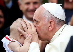 Pope Francis kisses a child as he arrives at the Catholic University during his one-day visit to Albania, in Tirana