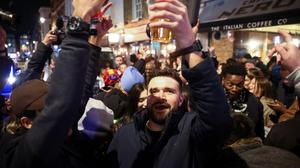 People hold up beverages as they party on a street in Soho, as the coronavirus disease (COVID-19) restrictions ease, in London, Britain April 12, 2021. REUTERS/Henry Nicholls