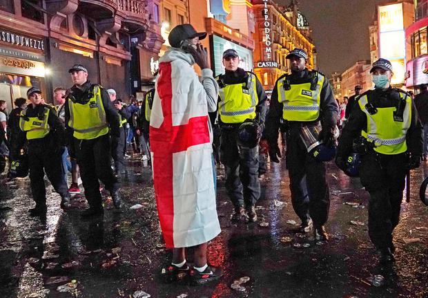 A fan stands with police in central London on Sunday. Photo: Aaron Chown/PA