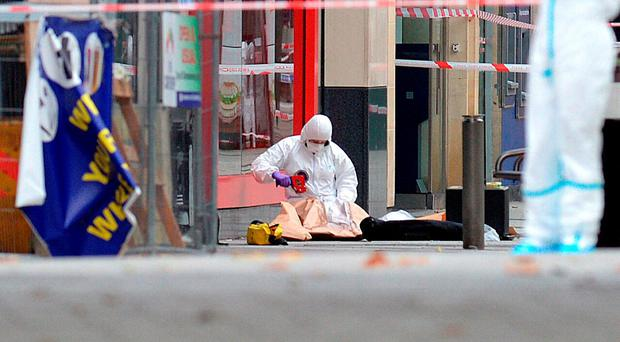 Forensic officers at the scene in Queen Street, near Cardiff Castle after the bodies of a man and a woman were found in Cardiff city centre. PRESS ASSOCIATION Photo. Picture date: Wednesday September 28, 2016. A man has been arrested and is being questioned by South Wales Police, who are not looking for anyone else in connection with the deaths. See PA story POLICE Cardiff. Photo credit should read: Ben Birchall/PA Wire