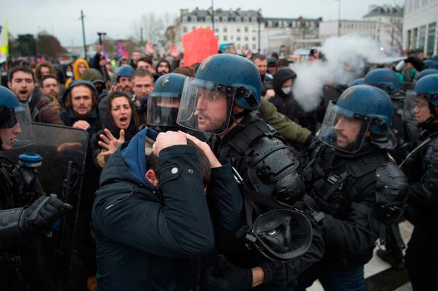 Street battle: Riot police and protesters clash in the city of Nantes yesterday during nationwide strikes. Photo: Getty Images