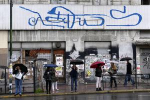 """People wait for a bus in Athens under a huge slogan reading """"wrong""""."""