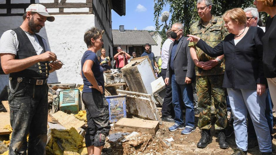 German Chancellor Angela Merkel, right, talks to residents during a visit to the flood-damaged village of Schuld near Bad Neuenahr-Ahrweiler, Germany, Sunday July 18, 2021. After days of extreme downpours causing devastating floods in Germany and other parts of western Europe the death toll has risen.