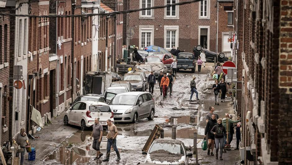 People walk through a damaged street after flooding in Chenee, Province of Liege, Belgium, Friday July 16, 2021. Severe flooding in Germany and Belgium has turned streams and streets into raging torrents that have swept away cars and caused houses to collapse. (AP Photo/Valentin Bianchi)
