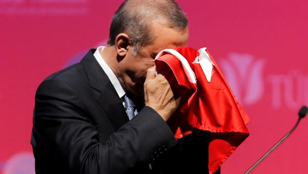 Turkey's President Tayyip Erdogan kisses a handmade Turkish flag, given to him as a gift from Ugandan university student Cemil (not pictured), during a graduation ceremony in Ankara.
