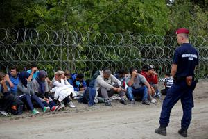 A policeman guards migrants detained after crossing the border from Serbia near Asttohatolom, Hungary