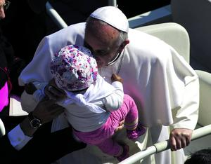 Pope Francis kisses a baby as he arrives in St. Peter's Square at the Vatican for his weekly general audience, Wednesday, May 8, 2013. (AP Photo/Andrew Medichini)