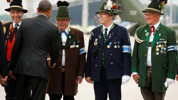 U.S. President Barack Obama shakes hands with men in traditional Bavarian attire as he departs Munich, Germany, at the end of the G7 Summit yesterday