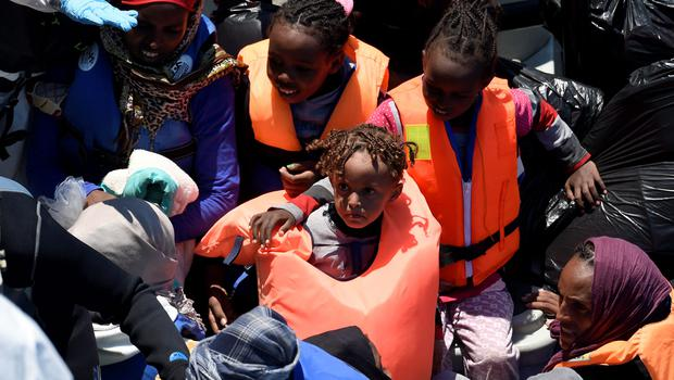Young illegal migrants smile as they're taken aboard the LÉ Eithne