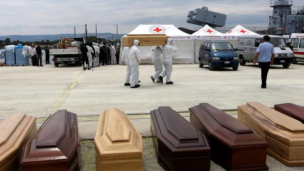 Emergency workers carry a coffin as 17 bodies are taken ashore at the Sicilian harbour of Augusta yesterday. Photo: Reuters