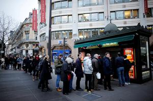 "People queue to get a copy of satirical French magazine Charlie Hebdo new issue titled ""Tout est pardonne"" (""All is forgiven"") in Paris yesterday."