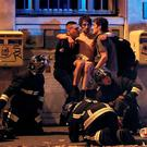 French fire brigade members aid an injured individual near the Bataclan concert hall following fatal shootings in Paris