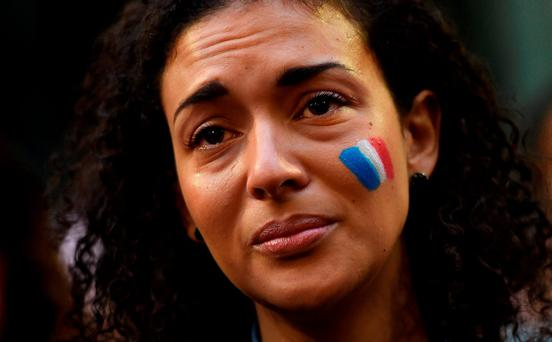 A woman weeps at a vigil held by the local French community in Sydney, as Australians express their solidarity with France