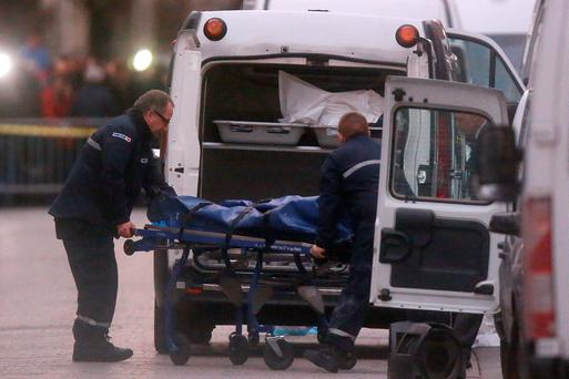 Medical personnel put a body into the back of an ambulance after the shoot-out in Saint Denis