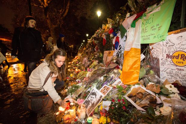 Mourners reflect on the city's great loss at floral tributes outside the Bataclan theatre in Paris
