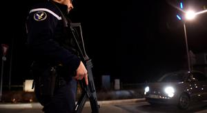 An armed French gendarme stands guard during the control of vehicles at the French-Swiss border in Divonne-les-Bains, near Geneva,