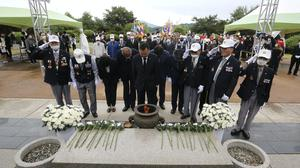 Veterans, wearing white caps, and other participants pay their respects during a ceremony to mark the 70th anniversary of the outbreak of the Korean War in Cheorwon, South Korea (Ahn Young-joon/AP)