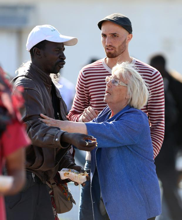 A volunteer calms a man in a food queue for migrants in Calais, France, as tensions remain high following overnight clashes between rival groups waiting to try and cross the Channel to Britain. Photo: PA
