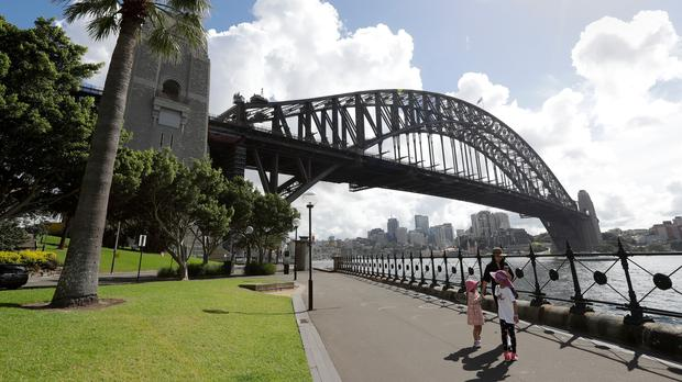 A woman and two children walk under the Harbour Bridge in a popular area in Sydney, Australia (Rick Rycroft/AP)
