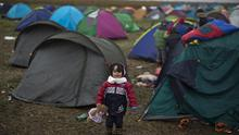 Syrian refugee child Jana Makkiyeh, three, holds a teddy bear while standing near her family's tent at a makeshift camp for asylum seekers in Roszke, southern Hungary (AP)