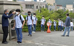 Students wearing face masks to help protect against the spread of the new coronavirus stand in a queue to have their body temperatures checked before entering their classrooms at a high school in Ulsan, South Korea (Bae Byung-soo/AP)