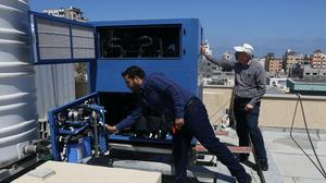 Engineers Raed Nakhal from Palestine Children Relief Fund, right, and Abdullah Dewik check the GEN-M machine that generates safe drinking water in Gaza City (Adel Hana/AP)