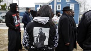 A woman wears a shirt featuring a photograph of Jerame Reid who was shot dead by police (AP)