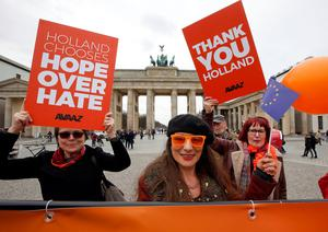 People hold placards to support the election results in the Netherlands during a demonstration in front of the Brandenburg Gate in Berlin