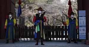 Officials wearing traditional guard uniforms in front of the Deoksu palace in central Seoul (Lee Jin-man/AP)