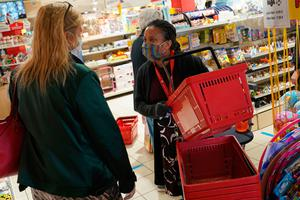 Back in business: A shop assistant wearing a protective face mask hands a customer a shopping basket at the entrance to a toy store that was opening for the first time yesterday since March in Berlin. Photo: Sean Gallup/Getty
