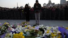 A man and a woman pray after laying flowers at the site of the stampede in Shanghai. (AP)