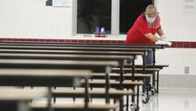 Garland Independent School District custodian Camelia Tobon wipes down tables in the cafeteria at Stephens Elementary School in Rowlett, Texas LM Otero/AP)
